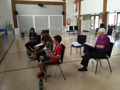 Gary Potter, who plays the Toymaker, sits behind members of the children's ensemble.